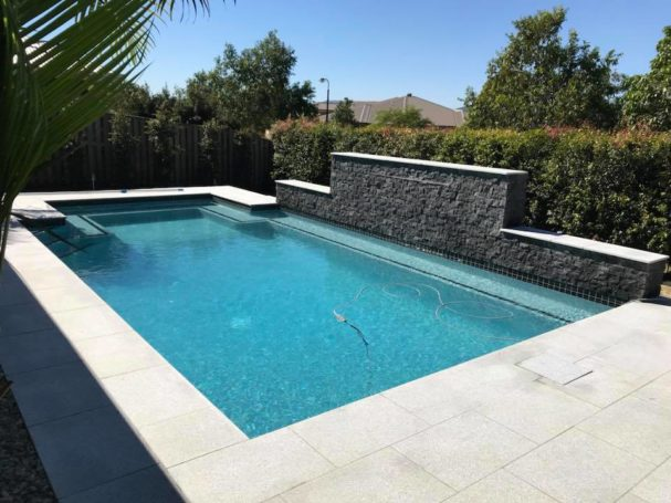 concrete swimming pool with granite tiles and water feature on the Gold Coast
